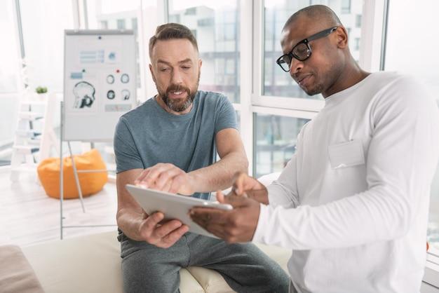 Dispositivo moderno. homem barbudo simpático sério olhando para a tela do tablet enquanto falava com seu médico