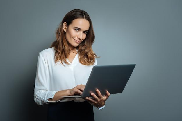 Dispositivo necessário. mulher bonita, positiva e encantada, segurando seu laptop e usando-o para trabalhar, em pé contra um fundo cinza