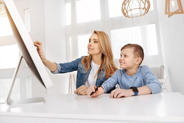 Dispositivo sensorial. agradável jovem encantada sorrindo e usando um monitor sensorial enquanto está sentada junto com seu filho