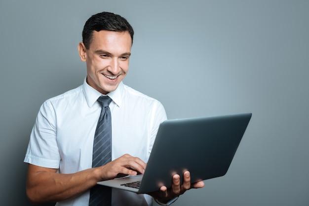Dispositivo tecnológico. jovem gerente alegre e positivo segurando um laptop e sorrindo enquanto trabalha nele