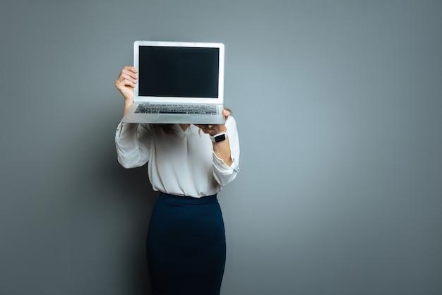 Dispositivo tecnológico. mulher jovem e simpática segurando seu laptop e escondendo o rosto atrás dele enquanto está de pé contra um fundo cinza