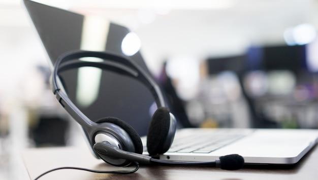 Dispositivos de fone de ouvido na mesa de escritório para o conceito de suporte de serviço ao cliente