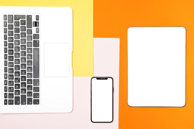 Dispositivos de maquete plana leigos com fundo colorido