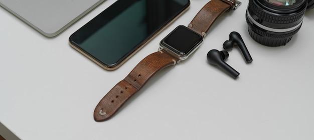 Dispositivos digitais na mesa branca com smartphone, smartwatch, fone de ouvido, lente e espaço de cópia