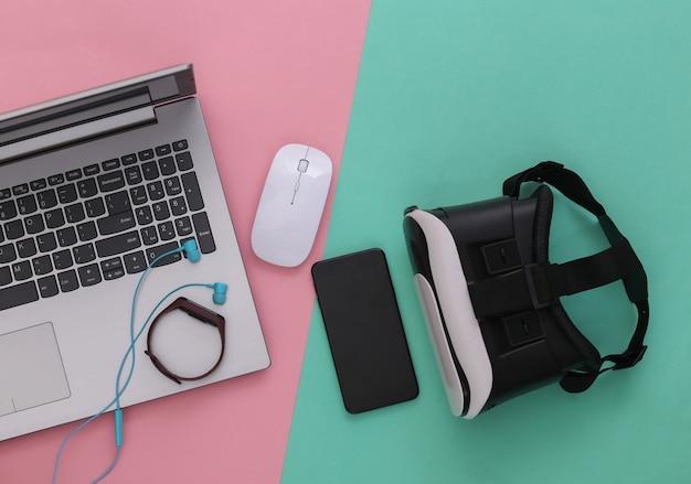 Dispositivos e dispositivos modernos da juventude em fundo azul-de-rosa. vista do topo. postura plana