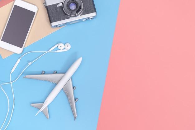 Dispositivos e objetos de vista superior de viagens para o viajante de negócios no espaço de cópia rosa amarela azul