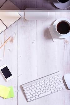 Dispositivos e suprimentos na mesa de escritório de madeira branca de negócios