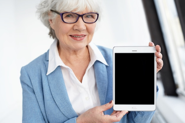 Dispositivos eletrônicos, dispositivos, tecnologia e conceito de conexão. mulher idosa elegante e alegre de cabelos grisalhos europeus com óculos apresentando tablet digital com display preto com copyspace para seu texto