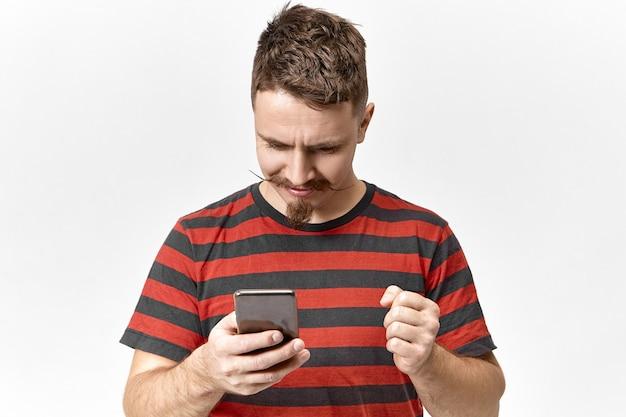 Dispositivos eletrônicos e comunicação. jovem bonito barbudo de camiseta preta e vermelha navegando na internet, comprando passagens de avião baratas com desconto usando telefone celular, com olhar impaciente e animado