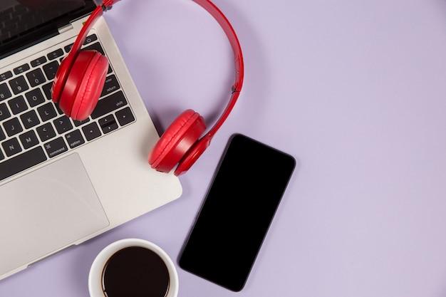 Dispositivos eletrônicos para ouvir música e uma xícara de café