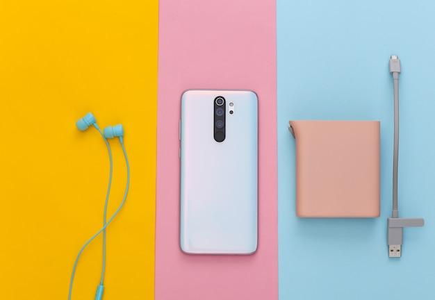 Dispositivos modernos. smartphone, fones de ouvido e pastel de banco de energia