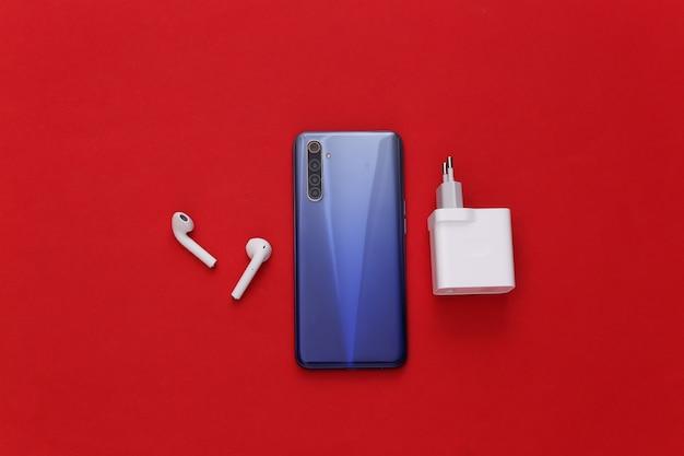Dispositivos modernos. smartphone moderno com fones de ouvido sem fio, carregador vermelho