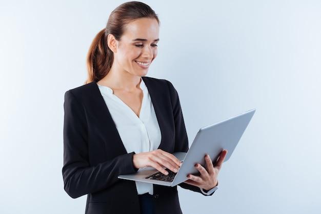Dispositivos portáteis. feliz alegre empresária inteligente segurando um laptop e olhando para a tela enquanto sorri