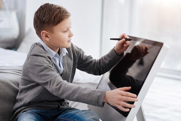 Dispositivos tecnológicos de última geração. menino fofo e agradável e feliz sorrindo e furando uma caneta stylus enquanto desenha em uma tela digital