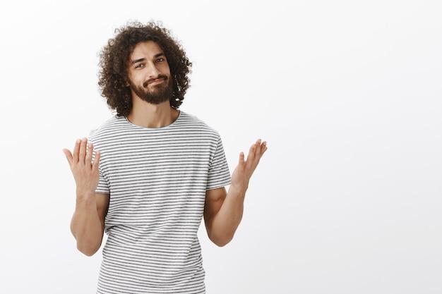 Disse que estava certo. lindo modelo oriental masculino com barba e cabelos cacheados, levantando as mãos e sorrindo, sentindo-se aliviado e dizendo finalmente