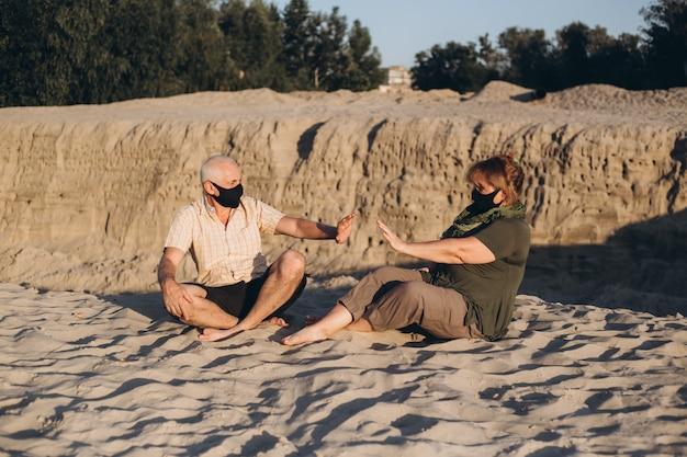 Distância social, fique seguro. casal de idosos com máscaras médicas para proteção contra coronavírus fora