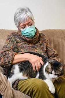 Distanciamento social do coronavírus devido a surto de pandemia. mulher idosa com máscara protetora, ficar em casa, acariciando seu gato.