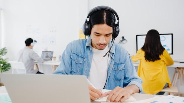 Distanciamento social do empresário ásia na nova situação normal para prevenção de vírus usando laptop apresentação para colega sobre o plano de videochamada enquanto trabalha no escritório em casa. estilo de vida após o vírus corona.