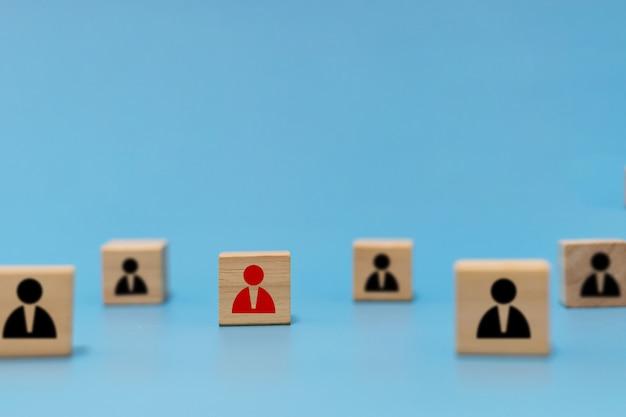 Distanciamento social. grupo de ícone de pessoa no cubo de madeira mantém o distanciamento social para evitar covid-19 sobre fundo azul. novo normal, prevenção de vírus, auto quarentena, conceito de distância social