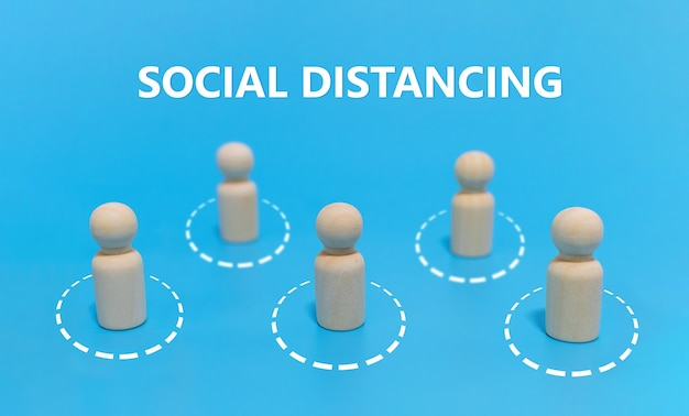 Distanciamento social. grupo de multidão de madeira mantém o distanciamento social para evitar covid-19 sobre fundo azul. novo estilo de vida normal, prevenção de vírus, auto quarentena, conceito de distância social