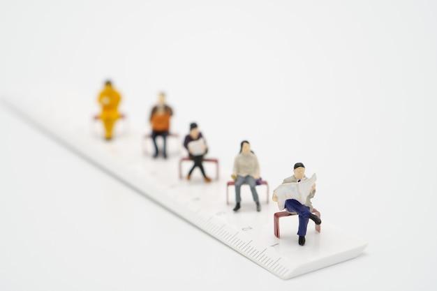 Distanciamento social. pessoas em miniatura ficam separadas para reduzir a infecção pelo vírus covid 19. manter distância social