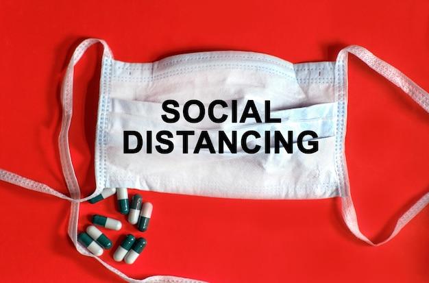 Distanciamento social - texto em uma máscara protetora, comprimidos em um fundo vermelho