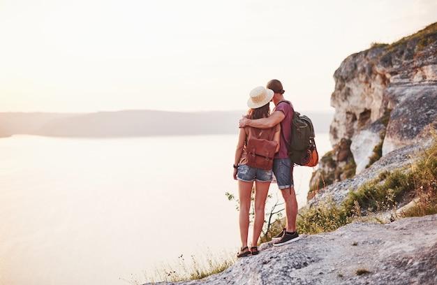 Distante. o jovem casal decidiu passar as férias de forma ativa na beira de uma linda rocha com um lago ao fundo.