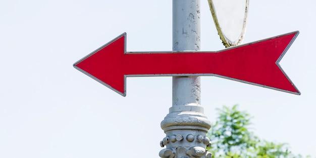 Distinta seta vermelha em um poste