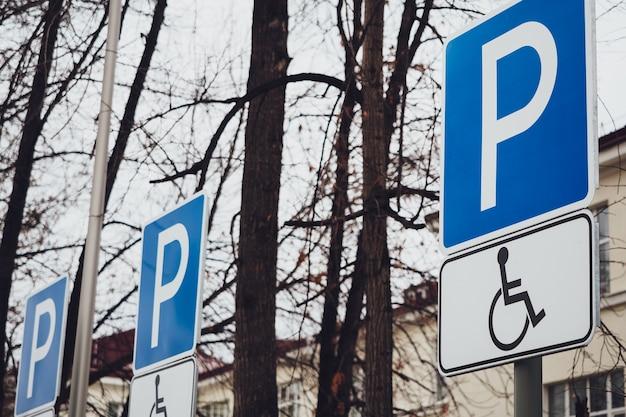 Distintivo azul estacionamento para pessoas com deficiência em um fundo de céu nublado e árvores