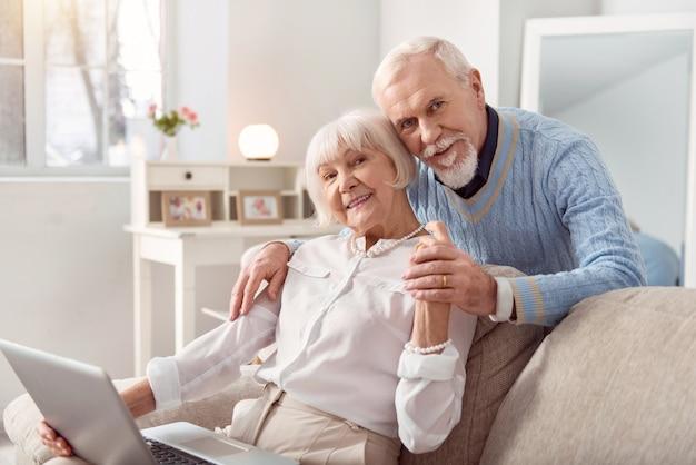 Distração agradável. homem idoso alegre abraçando sua amada esposa por trás enquanto ela está sentada no sofá e trabalhando no laptop