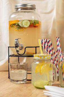 Distribuidor de bebidas naturais com suco cítrico caseiro sobre superfície de madeira, diferentes tipos de copos e jarras com sorvete e gelo