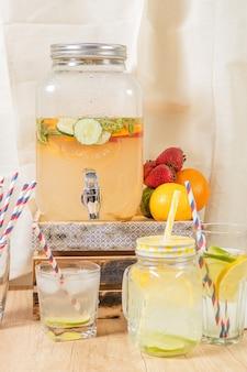 Distribuidor de bebidas naturais com suco cítrico caseiro sobre superfície de madeira, diferentes tipos de copos e jarras com sorvete