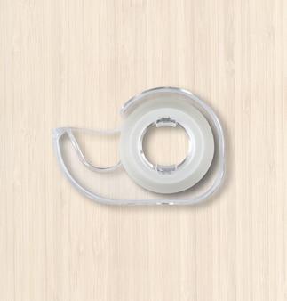 Distribuidor de fita adesiva transparente isolado em fundo branco de madeira
