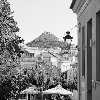 Distrito de plaka e colina lycabettus em atenas, grécia. fotografia em preto e branco, paisagem urbana