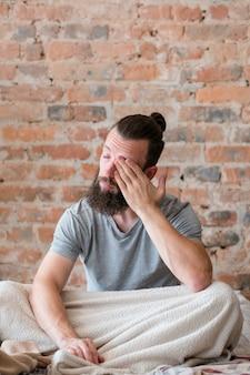 Distúrbio do sono. homem sentado na cama, esfregando os olhos e se sentindo mal. aparência cansada e com sono pela manhã. copie o espaço.