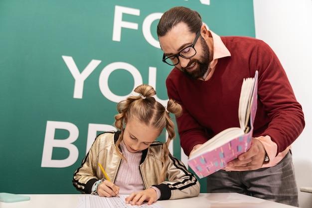 Ditado. professor adulto, de cabelos escuros, barbudo e usando óculos, ditando palavras para seu aluno