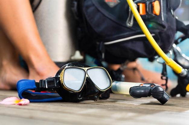 Divemaster e alunos do mergulhador curso de férias vestindo uma roupa de mergulho ou mergulhando em primeiro plano é um tanque de oxigênio