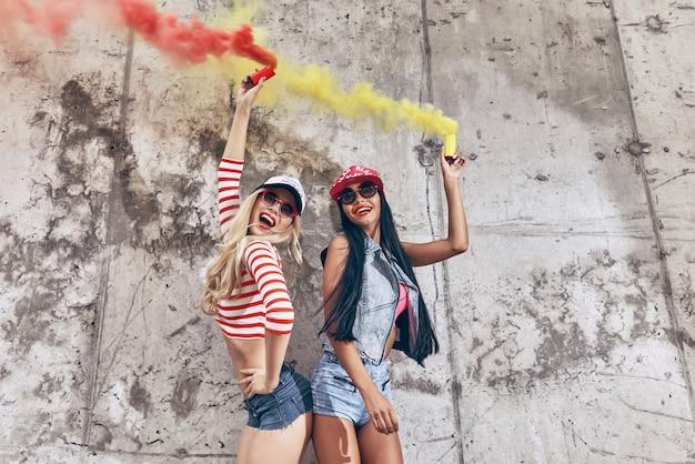 Diversão colorida. duas jovens felizes segurando bombas de fumaça e sorrindo enquanto posam contra a parede de concreto