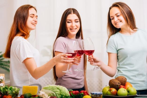 Diversão de festa feminina. variedade de alimentos saudáveis. mulheres jovens felizes tilintando taças de vinho tinto.