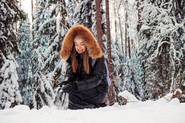 Diversão de inverno ao ar livre, uma jovem alegre jogando bolas de neve