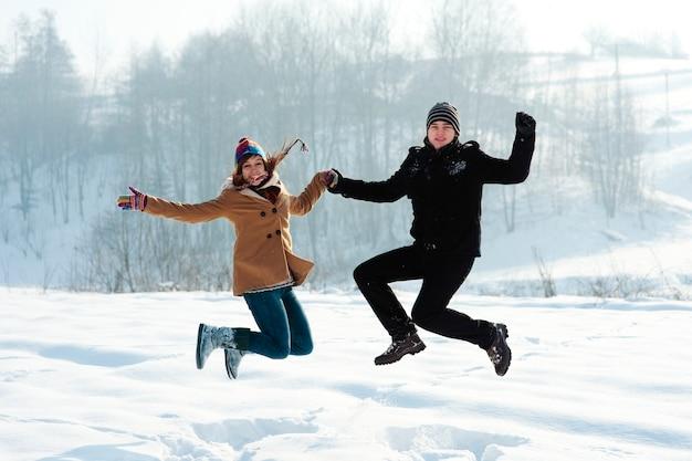 Diversão de inverno, jovem casal pulando ao ar livre