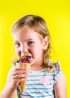 Diversão de verão férias conceito, menina criança loira bonita comer bagas de casquinha de sorvete waffle, fundo amarelo brilhante