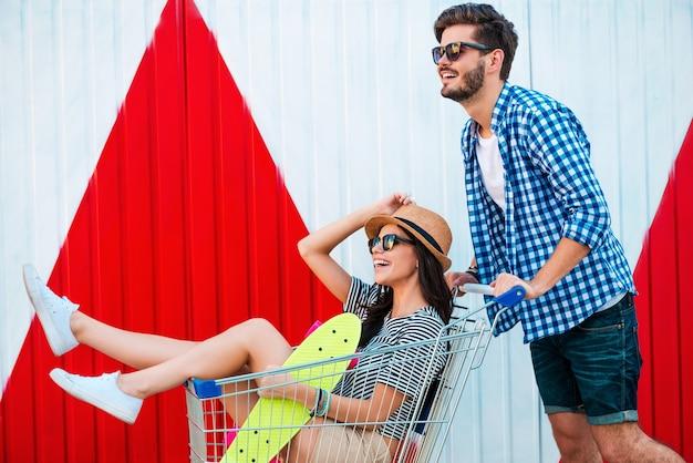Diversão despreocupada. vista lateral de uma jovem alegre sentada no carrinho de compras enquanto o namorado o empurra