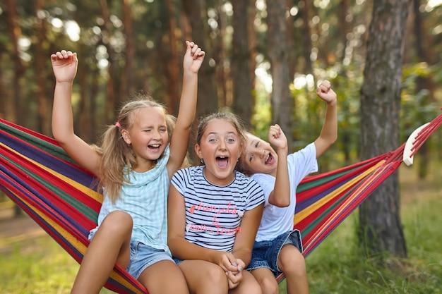 Diversão no jardim, crianças brincando em redes coloridas