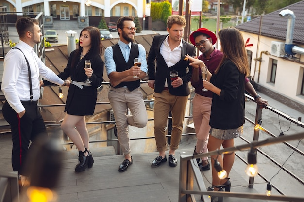 Diversão. os jovens comemoram, parecem felizes, fazem festa no escritório ou no bar. homens e mulheres bebendo álcool, conversando, rindo. férias, fim de semana, negócios e finanças, conceito de amizade. consolidação de equipe.