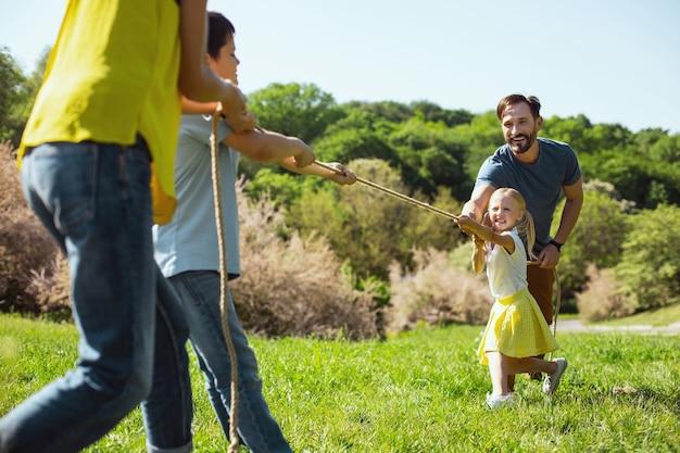 Diversão. pai amoroso e alegre ajudando a filha enquanto ela puxa uma corda com o irmão
