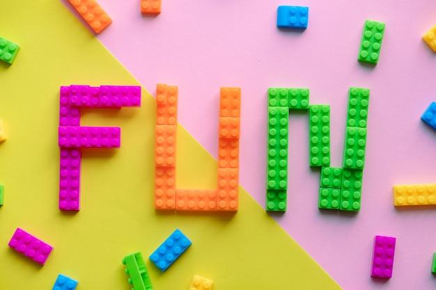 Diversão palavra soletrada com fundo de blocos de plástico