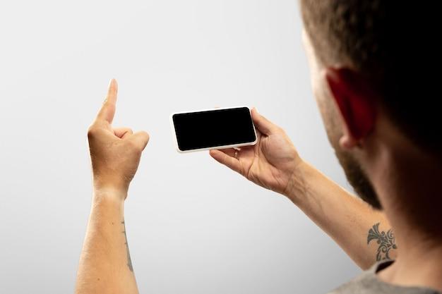 Diversão sincera feche as mãos masculinas segurando um telefone com a tela em branco durante online