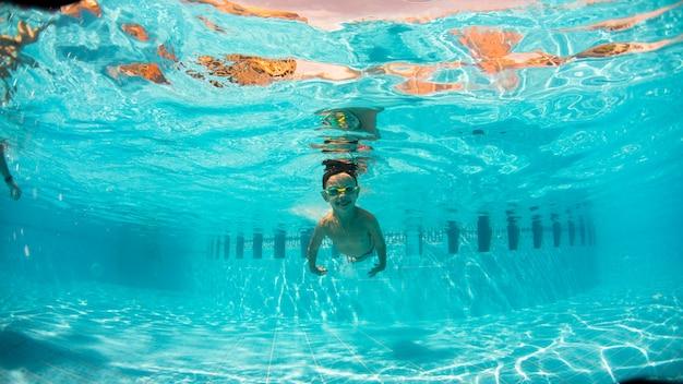 Diversão subaquática de menino na piscina com óculos de proteção. verão . diversão de férias de verão