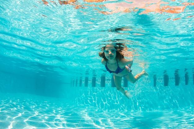 Diversão subaquática jovem na piscina com óculos de proteção. verão . diversão de férias de verão
